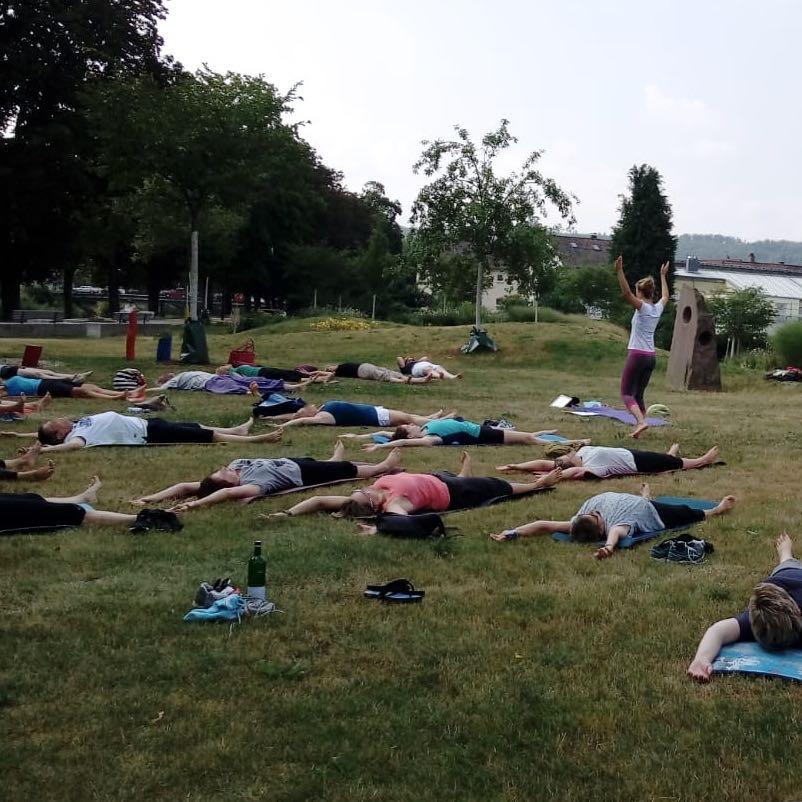 Outdoor-Yoga auf einer großen grünen Wiese im Schatten von großen Bäumen